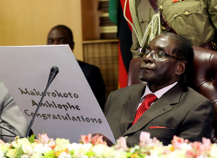 Zimbabwean President Robert Mugabe reads a card during his 93rd birthday celebrations in Harare, Zimbabwe, on Tuesday.  Picture: REUTERS/PHILIMON BULAWAYO
