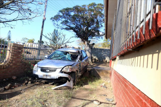 LETHAL WEAPON: The car that came crashing through a Mdantsane family's wall, damaging a tree and missing the house by centimetres, is being kept there until the wall is repaired Picture: SIBONGILE NGALWA