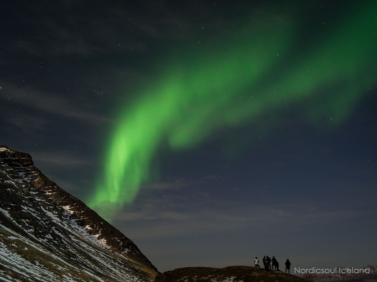A small group of people watching the Northern Lights dance over a snow-covered mountain in Iceland