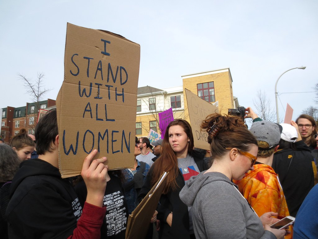 "A person holding a cardboard sign that says ""I stand with all women"" at a rally/march in front of their face."