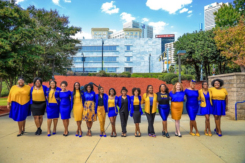 A group of 15 women wearing blue and yellow, standing in a line and smiling at the camera.