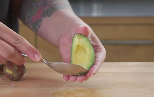 Using a spoon, separate the avocado from outer skin.
