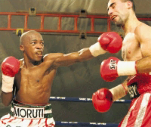 WHAM: Moruti 'Pretty Boy' Mthalane, left, lands a punch to the chin on Hussein Hussein during their fight in East London . Pic. Antonio Muchave. 05/07/08. © Sowetan.