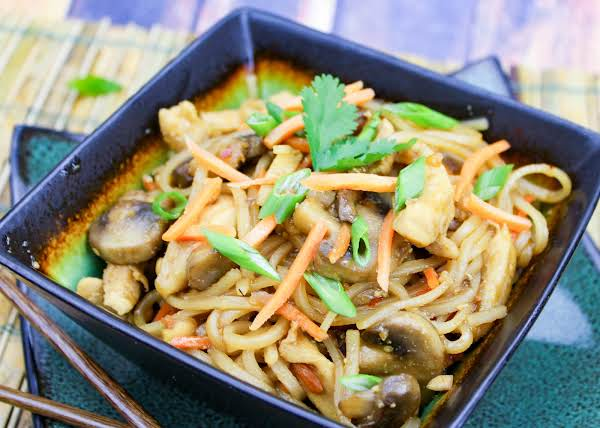 Dragon Noodles With Chicken In A Bowl With Scallions Sprinkled On Top.