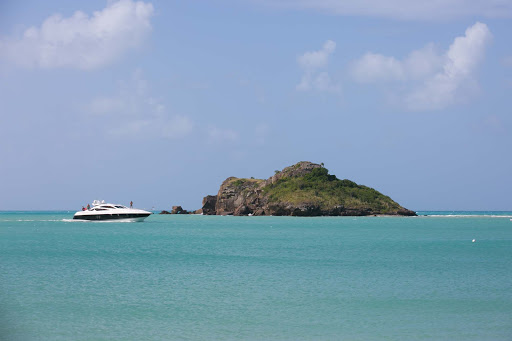 A pleasure boat passes a rock outcropping in Antigua.