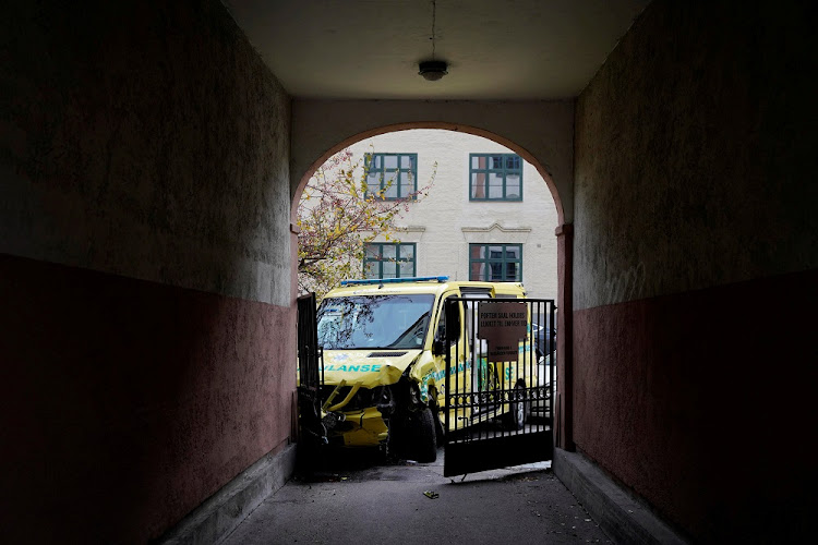 A damaged ambulance stands next to a building after an armed man who stole the vehicle was apprehended by police in Oslo, Norway, October 22, 2019.