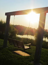 Photo: Sunset on a wooden swing for two overlooking a lake at Carriage Hill Metropark in Dayton, Ohio.