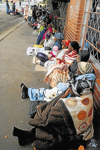 Social grant beneficiaries, mostly women, wait outside a Sassa office. Calls are being made to protect vulnerable people from unscrupulous lenders.