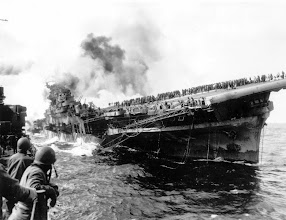 Photo: March 19, 1945: The USS Santa Fe lies alongside the heavily listing USS Franklin to provide assistance after the aircraft carrier had been hit and set afire by a single Japanese dive bomber, during the Okinawa invasion off the coast of Honshu, Japan. (AP Photo)