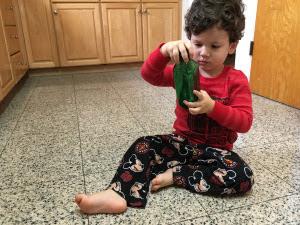 Toddler boy holding glitter bottle