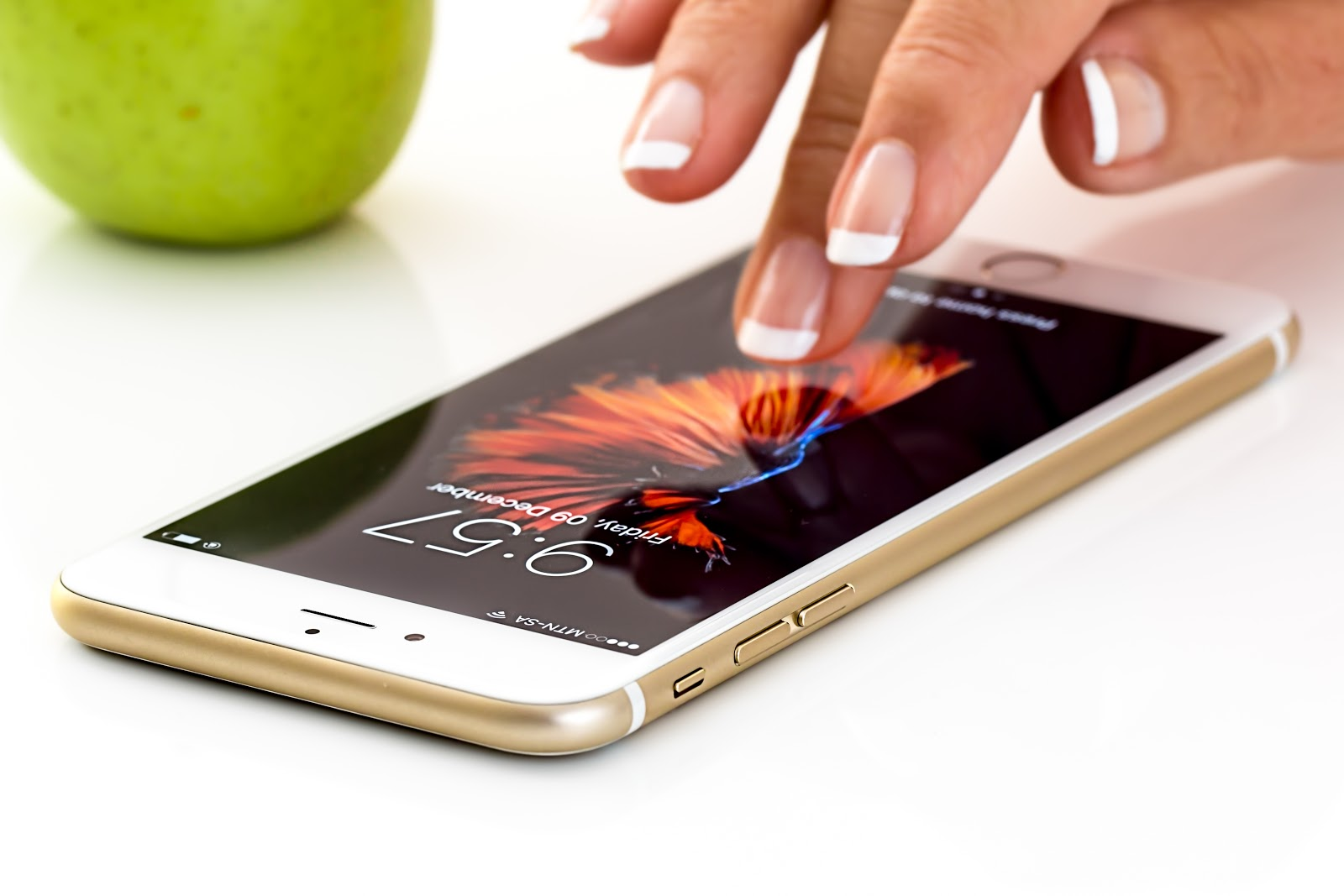 A middle finger hovers just above the screen of a white smartphone, with a green granny smith app in the top left hand corner of the scene