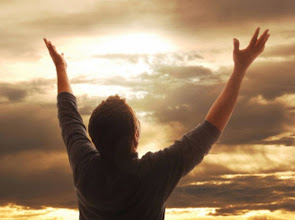 Photo: Man holding arms up in praise against golden sunset