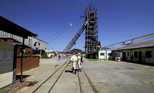 Mine workers walk past the pit head at Sibanye-Stillwater's Masimthembe shaft in Westonaria. Picture: REUTERS