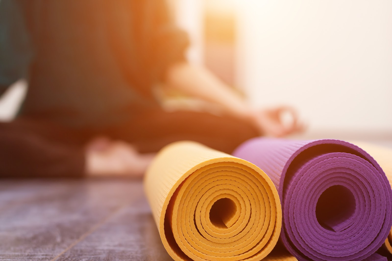 Yoga mats rolled up, woman in yoga pose, stress relief