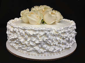 Photo: Wedding cake w/ruffle border & edible pearl bottom trim, topped w/fresh Ivory roses.