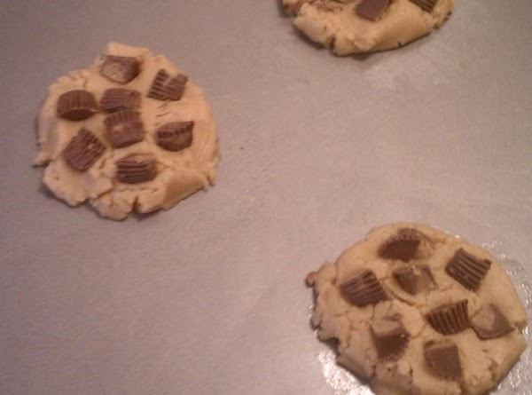 Push dough slightly flat and push about 7-8 pieces of peanut butter cup into...
