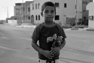 Photo: happy kid with flower  my recent album about street life of the Jisr az-Zarqa - the only Arab town in Israel that is located almost in the middle of country. I'll post more works taken during the 5 hours tour in this town.  my online prints shop - http://www.redbubble.com/people/stran9e/shop/photographic-prints  #streetphotography   #streettogs     #monochrome     #blackandwhite     #jisrazzarqa
