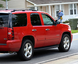 """Photo: The gas guzzling Chevy Tahoe is very popular around here. The guy in the background is bringing us into the 20th century to day by installing """"smart"""" electric meters. Nice, but more jobs lost. #allthingsred +AllThingsRed curated by +Lucille Galleli & +Stephen Thackeray"""
