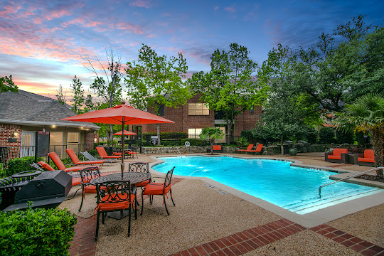 Swimming pool at dusk with lounge chairs, table, umbrella, and trees