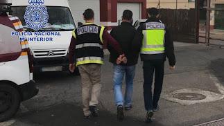 Dos policías nacionales llevan al detenido en El Ejido.
