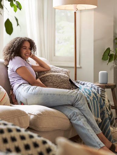 Woman sitting on living room couch with a Nest speaker on side table.