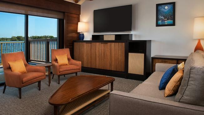 A living room overlooking Seven Seas Lagoon that features chairs, a coffee table and a flat screen TV