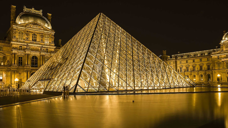 The Louvre Pyramid, in front of the Louvre Palace, illuminted at night in Paris.