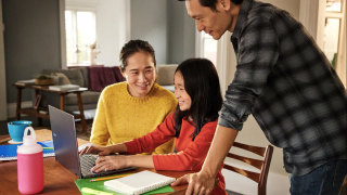 man woman and young girl look at computer together