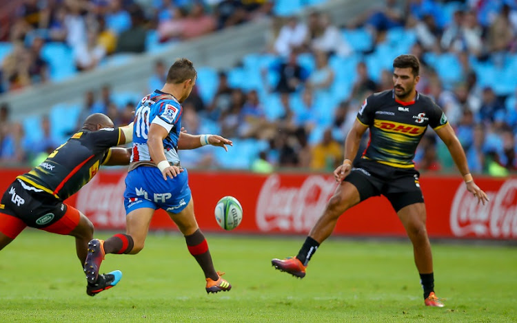 Handre Pollard of the Vodacom Bulls puts through a ball between Bongi Mbonambi of the DHL Stormers and Damian de Allende of the DHL Stormers during the Super Rugby match between Vodacom Bulls and DHL Stormers at Loftus Versfeld on February 16, 2019 in Pretoria, South Africa.