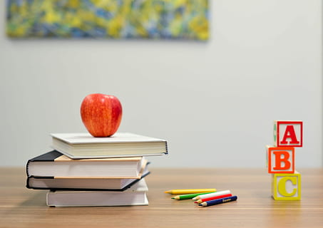 teacher desk has stack of books with apple on top of books, colored pencils, and stacked ABC blocks