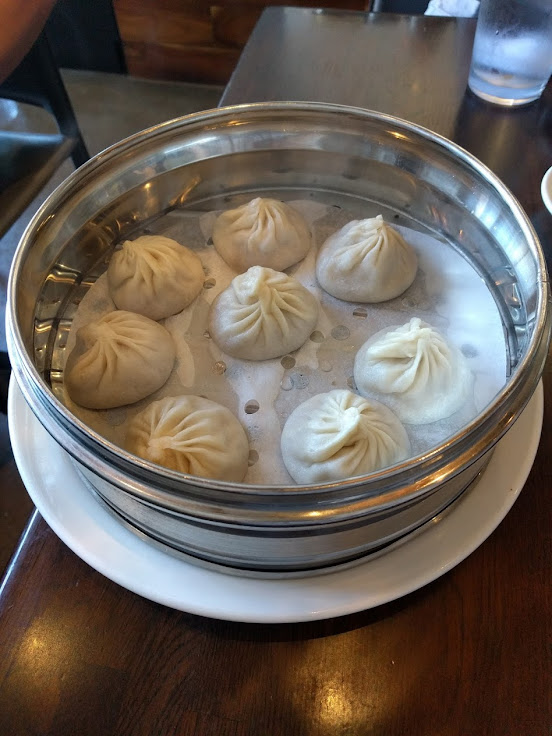 Xiao Long Bao soup dumplings sitting in their steamer.