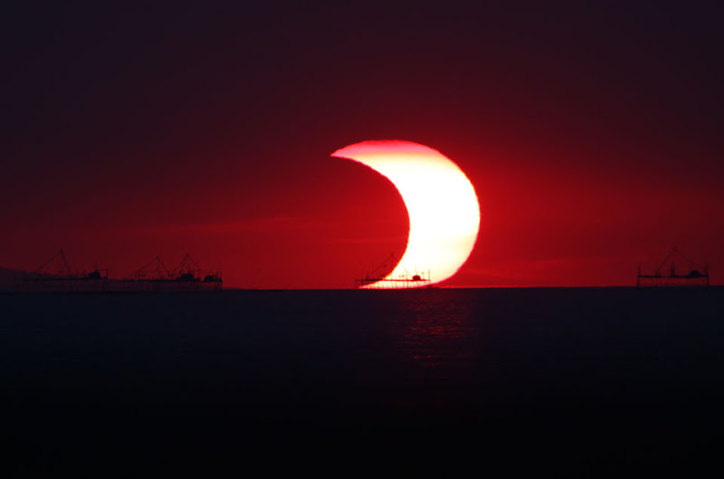 Photo: A Partial Eclipse Over Manila Bay Credit & Copyright: Armando Lee (Astron. League Philippines), F. Naelga Jr., 100 Hours of Astronomy (IYA2009) http://apod.nasa.gov/apod/ap120520.html  What's happened to the setting Sun? An eclipse! In early 2009, the Moon eclipsed part of the Sun as visible from parts of Africa, Australia, and Asia. In particular the above image, taken from the Mall of Asia seawall, caught a partially eclipsed Sun setting over Manila Bay in the Philippines. Piers are visible in silhouette in the foreground. Eclipse chasers and well placed sky enthusiasts captured many other interesting and artistic images of the year's only annular solar eclipse, including movies, eclipse shadow arrays, and rings of fire. Today parts of the Sun again will become briefly blocked by the Moon, again visible to some as a partial eclipse of a setting Sun. A small swath of Earth, however, will be exposed to the unusual ring of fire effect when the Moon is completely surrounded by the glowing light of the slightly larger Sun.