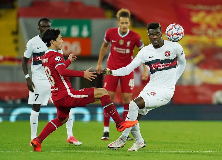 Midtjylland's Sory Kaba in action with Liverpool's Takumi Minamino