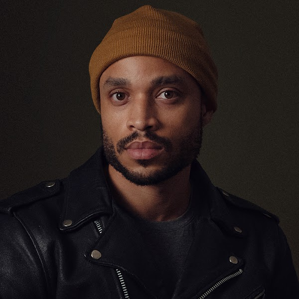 Portrait of artist in a brown beanie in front of a black background.