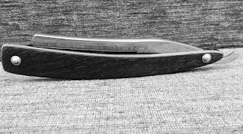 side view of straight razor blade on table