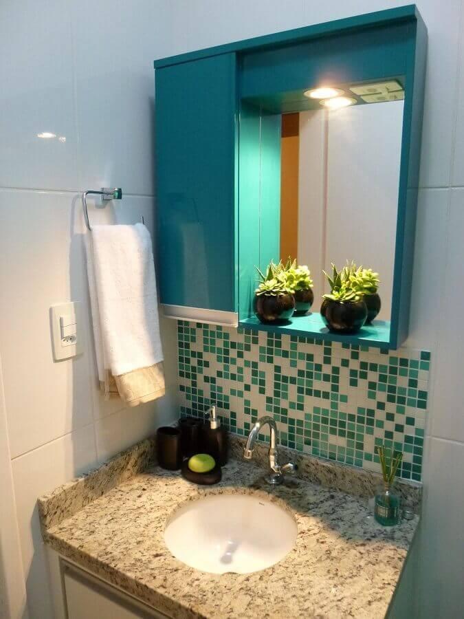 Banheiro simples com azulejo branco e pastilhas verde somente na parede acima da pia, armário azul e pia de mármore.