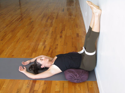 Viparita Karani (legs up the wall and sitting bones tipping over a bolster)