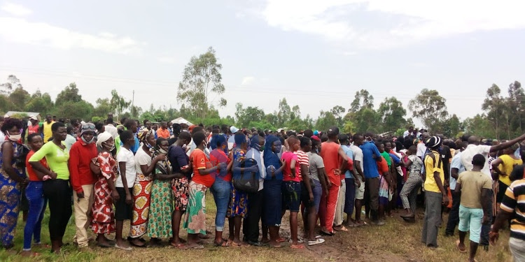 Mourners and locals line up at Kadiju Primary School to view the body of musician Abenny.