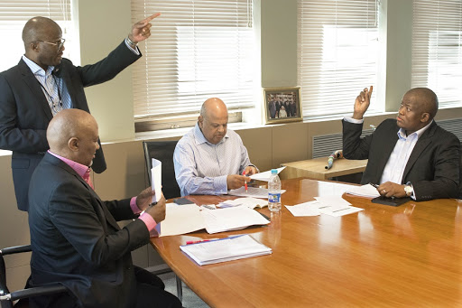 Dondo Mogajane points as former finance minister Mcebisi Jonas, sitting, left, former finance minister Pravin Gordhan, centre, and former Treasury director-general Lungisa Fuzile work on a budget presentation. Picture: TREVOR SAMSON
