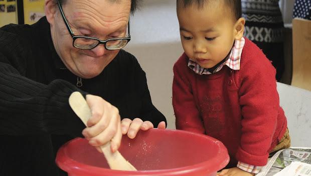 personne handicapée mentale avec un petit enfant asiatique font la cuisine