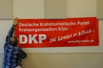 Genosse befestigt das Transparent: «Deutsche Kommunistische Partei Kreisorganisation Köln. DKP Die Linken in Kölle… www.dkp-koeln.de».