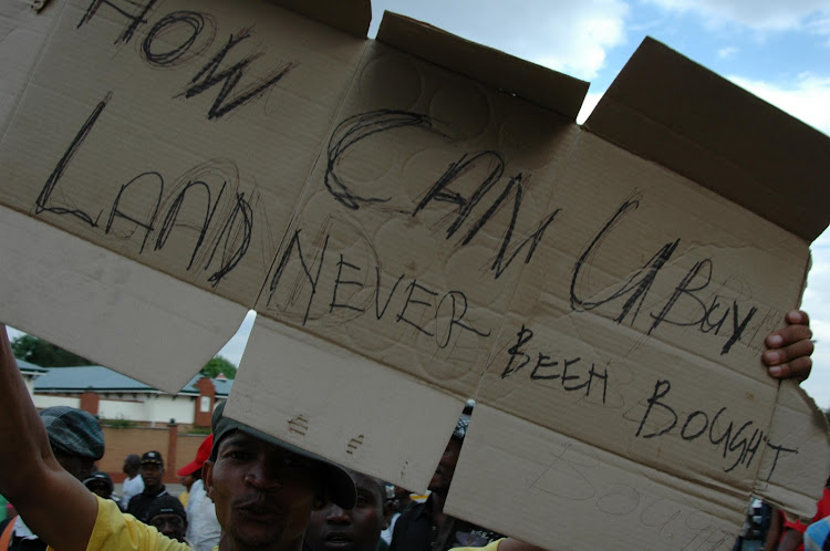 How Can U buy land Never Been Bought, placard held by an ANCYL supporter.