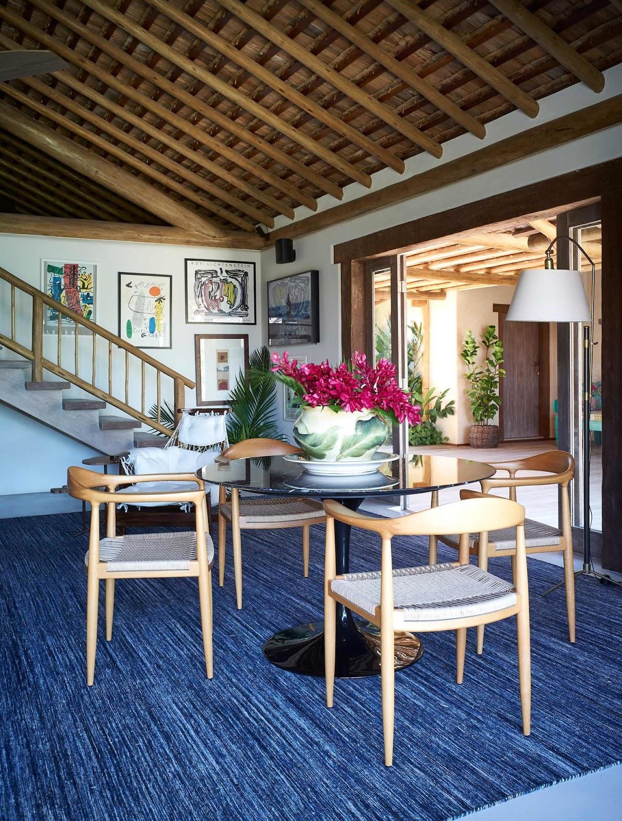 projeto casa de praia com tapete azul, cadeiras de madeira e telhado