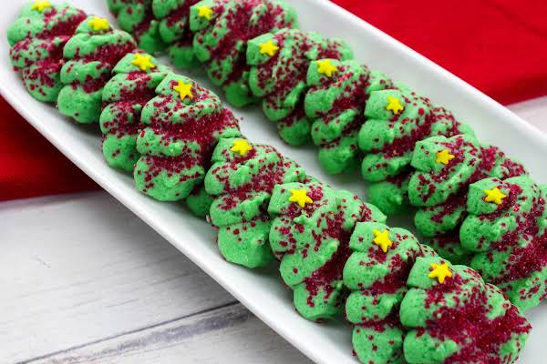 A Plate Of Decorated Christmas Tree Spritz Cookies.