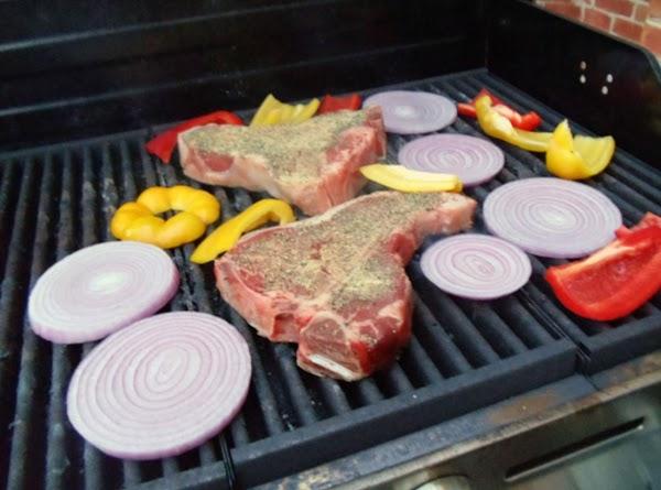 Place steak in center of grill - over medium ash-covered coals.  Arrange vegetables...