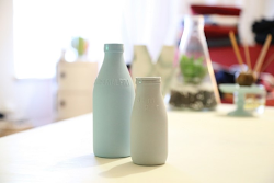 Two small milk jugs on a table in a kitchen