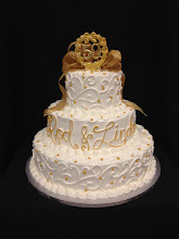 Photo: Fancy 3-tier stacked cake featuring white Town&Country w/gold dot border on each tier w/writing on middle tier. Gold French ribbon bow & 50th piece toppers.