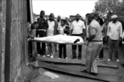 DEAD END: Etwatwa police remove the body of cop killer Mpiliso Ndlovu, who is also accused of killing nine people. Circa 03/ 2009. © Sowetan. Pic. Dan Fuphe.