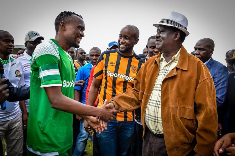 Gor Mahia Striker Jacques Tuyisenge with SportPesa CEO Ronald Karauri and AU Special Envoy Raila Odinga during a past match.