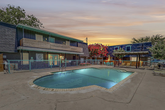 Apartment pool view with building in background at dusk